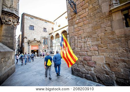 BARCELONA, SPAIN - September 16, 2017: People walk with Catalonian flag on the street in Barcelona. Campaign for voting for independence referendum from Spain