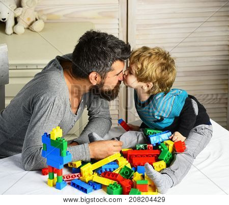 Man and boy play together on wooden wall background. Son kisses father in his nose making colorful toy bricks constructions. Family and childhood concept. Dad and kid build of plastic blocks