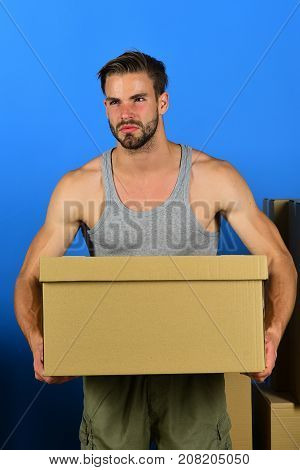 Man Standing Among Cardboard Boxes And Holding One