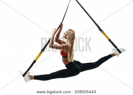 Beautiful young fitness woman in sportswear doing a split exercising with suspension straps isolated on white background