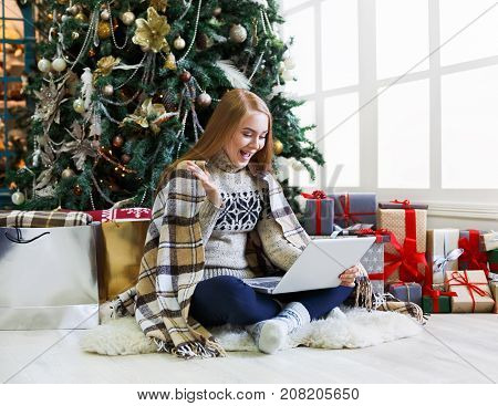 Surprised girl with laptop sitting at christmas tree background. Happy woman got greeting email from online shop with discount at winter sale. Holiday home atmosphere among present boxes, copy space