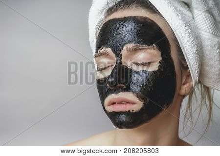 Black mask on woman face, smiling, skincare, cleansing pore, against acne