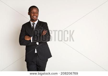 Successful african american in suit stands with arms crossed. Portrait on isolated white background, copy space