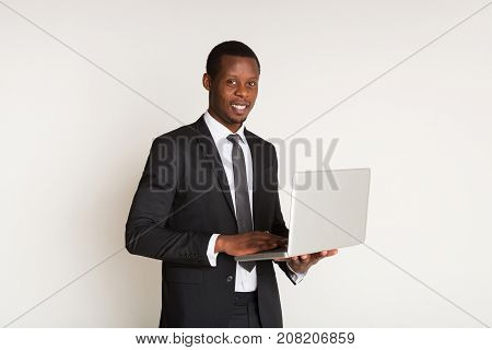 Successful businessman in stylish suit stands half sideways, holding laptop at hands. Portrait. Looking at the camera, copy space