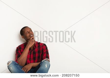 Smiling, pensive young black man sits leaning on the wall in casual looking aside at white studio background. Boy in checkered shirt sitting with crossed legs. Crop, close up, copy space