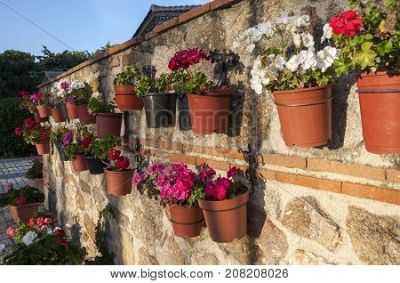 Flower pots hanged of the wall. Photo taken in hermitage of Our Lady of Remedies (Nuestra Señora de los Remedios) Colmenar Viejo Madrid Spain.