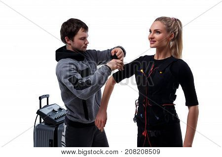 Trainer helps woman attaching electrode on ems suit isolated on white background