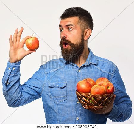 Farmer With Surprised Face Holds Red Apple. Man With Beard