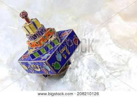 Festive colorful enameled Hanukkah dreidel on a soft white background