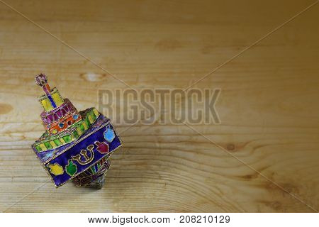 Bright and colorful enameled metal Hanukkah dreidel on a wood table