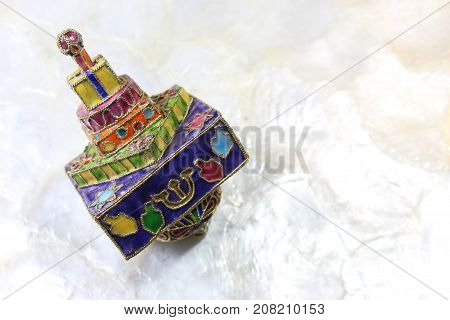 Brightly colored cloisonne Hanukkah dreidel on a soft white background