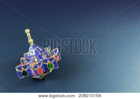 Star shaped enameled Hanukkah dreidel on a blue background with space for text, horizontal aspect