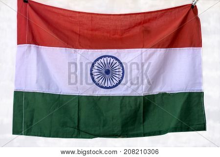 Crumpled Indian flag made of cotton fabric is fixed on a white wall with clothespins.