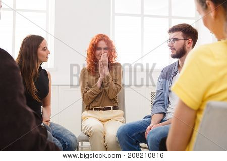 Meeting of support group. Young despaired woman crying during rehab group therapy. Psychotherapy, depression, life issues concept