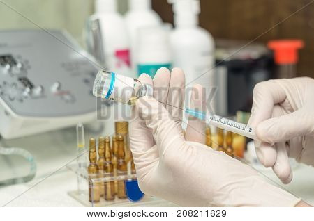 Doctor's hand with medical gloves and syringe needle and medicine vial. The needle sticks through the sterile membrane. Injection cosmetology. Anti-aging device on background.