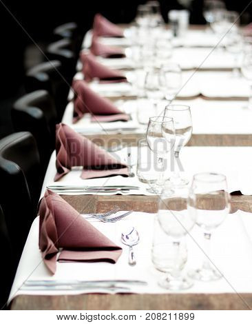 Restaurant Table Setting with Glasses Silverware and Napkins on Vintage Wooden Table with Chairs closeup. Focus on Forks