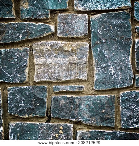 Obsolete Stone Wall Background with Various Shape Weathered Blocks closeup Outdoors