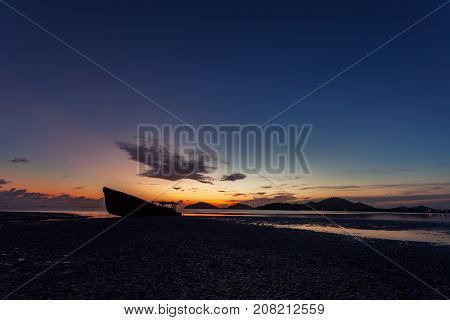 shipwreck on beach in the andaman sea with beautiful sunrise or sunset in phuket thailand
