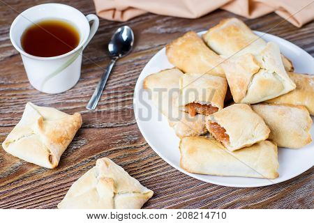 Little apple pies or apple turnovers with cinnamon on a white dish with tea cup and ripe apples in background, top view