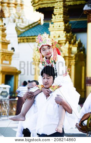 17 December 2016 young myanmar childern in traditional cloth ride the neck of his cousin walking around the shwedagon pagoda in buddhism ordained ceramony in yangonmyanmar