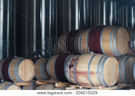 wine barrels deposited in a pile in front of chrome metallic fermentation tanks in a winery