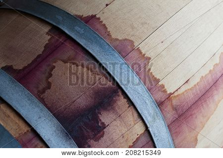 front view closeup of a wine oak wood barrel texture stained with red tannins