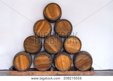 Oak barrels with wine in a winery laid out in the shape of a triangle on a white background.