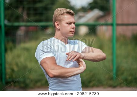 A man does a warm-up, in a city in nature, in summer in a T-shirt, warms up before jogging, stretching. The concept of safe sports. Athlete in nature.