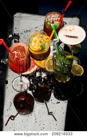 Party and summer vacation. Alcoholic beverage and fruit at restaurant. Drink and food. Fruit slice and cocktail glass at bar. Cocktails isolated on black background with mojito.