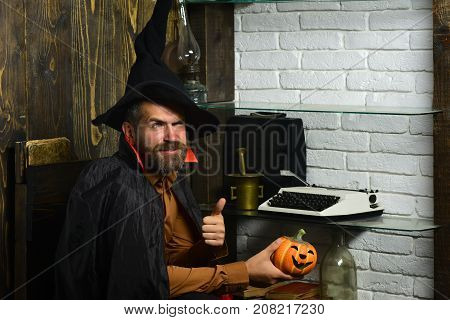 Halloween holiday celebration concept. Man in witch hat and cloak showing thumbs up. Wizardry and witchcraft. Wizard sitting with pumpkin on wooden wall. Magic and evil spell.