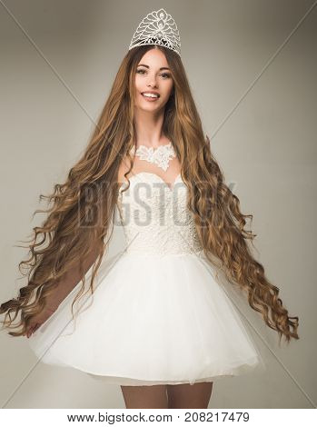 Girl has fashionable makeup and healthy hair on grey background. Woman with long hair white dress and crown. Haircare and prom queen. Beauty salon and wedding fashion. Hairdresser and cosmetics.