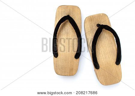 Old wooden Japanese sandal isolated on white background. It is a form of traditional Japanese footwear that resemble both clogs and flip-flops.