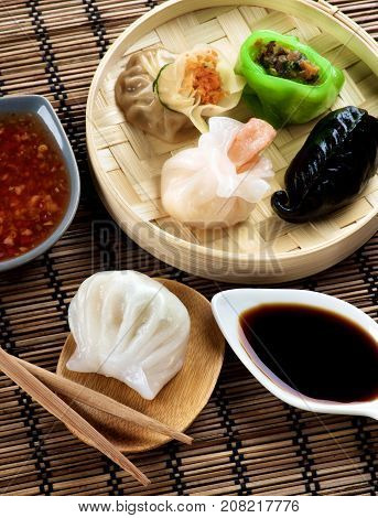 Assorted Dim Sum in Bamboo Steamed Bowl and Ika with Shrimps on Wooden Plate with Red Chili and Soy Sauces and Chopsticks closeup on Straw Mat background
