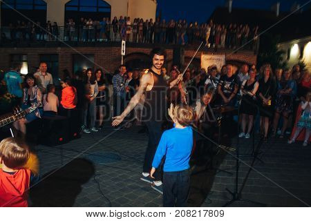 MINSK BELARUS.JULY 22 2017 Man playing the violin on the street The boy congratulates the street musician