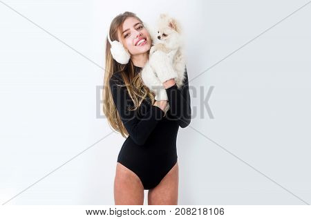 Dog in hand of woman on white background. Girl with happy face in gloves and ears. Xmas party and vacation. Woman with small dog of Pomeranian Spitz. New year of dog and winter holiday celebration.