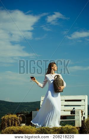 Model with alcohol drink on sunny day. Woman with glass of red wine and wicker bottle. Summer vacation holidays and celebration. Girl in white dress posing on blue sky. Winery tour concept.