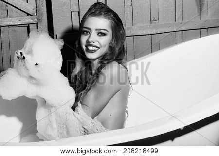 One beautiful sensual playful flirtatious young woman with long hair in blue knitted cloth sitting in white bath tub playing with soap foam indoor on wooden background horizontal picture