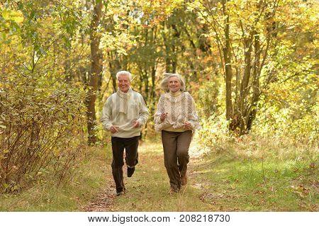 portrait of beautiful senior couple running   in the park