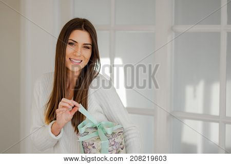 Smiling young sophisticated woman in elegant white interior home, holding a beautiful present round box, pulling the ribbon and opening the present, looking and smilig at camera.