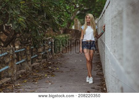 Beautiful blonde in a white t-shirt and short denim shorts standing at the White picket fence in an urban alley. Women's hands with a tattoo. Urban fashion.