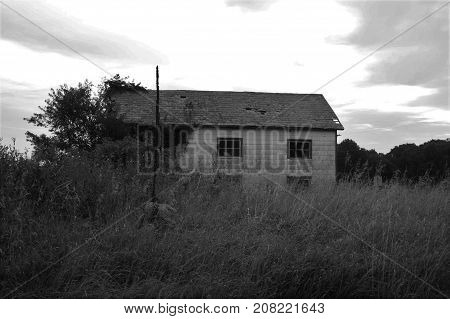 Old, empty home surrounded by tall grass
