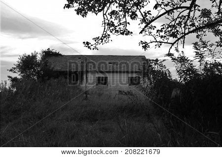 Old empty house sitting on an overgrown field