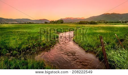 Vast grassland and winding river at dawn in summer with beautiful sky. Taken in Heber Utah USA.