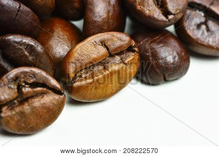 Close-up photo of grains of roasted black coffee on a white background with space for text and with blurred background
