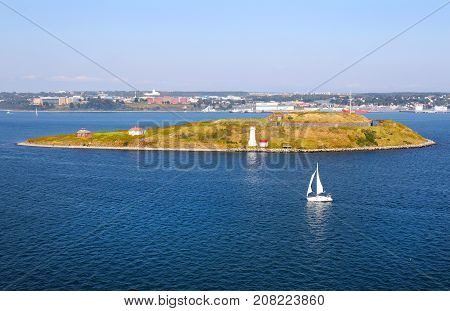 Lighthouse on Georges Island National Historic Site,  with a sailboat in the Halifax Harbor on a bright sunny day in September in Halifax, Nova Scotia
