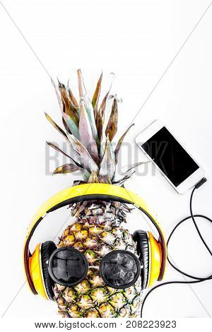 Cool pineapple in sunglasses is music lover. White background top view.