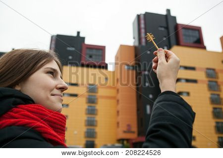a girl holds the keys to the apartment on the background of new buildings