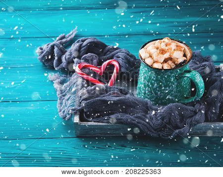 Hot chocolate with marshmallows on green background. Christmas winter still life with red candy canes in heart shape