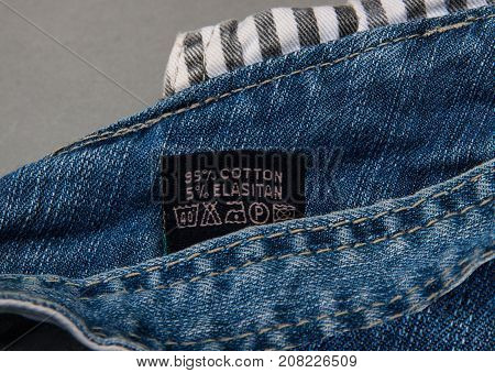 black fabric label on jeans closeup. composition. Clothing label with laundry care instructions