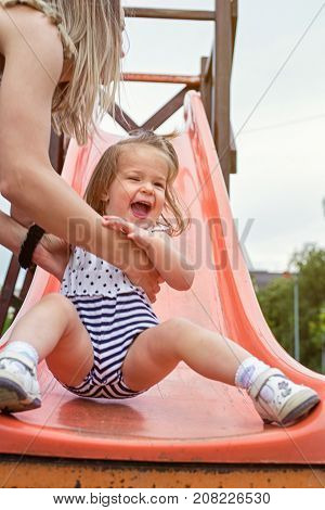 Happy smiling girl sliding down on slide at playground